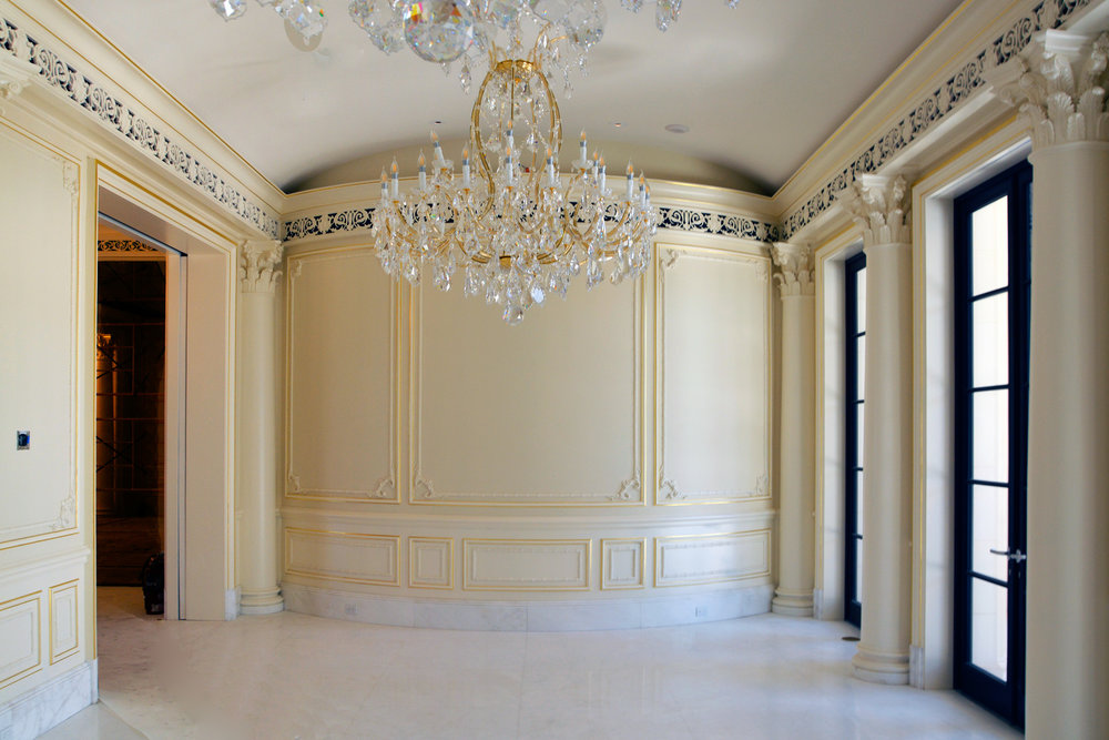 A full room with plaster grilles, gilded plaster details, and columns
