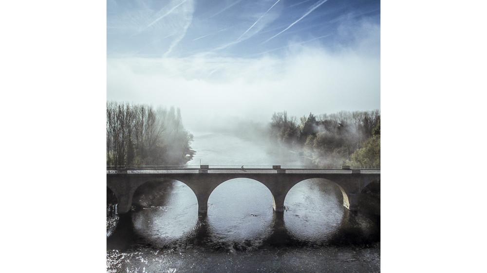 Cyclist crossing the Dordogne river, France -By erallion