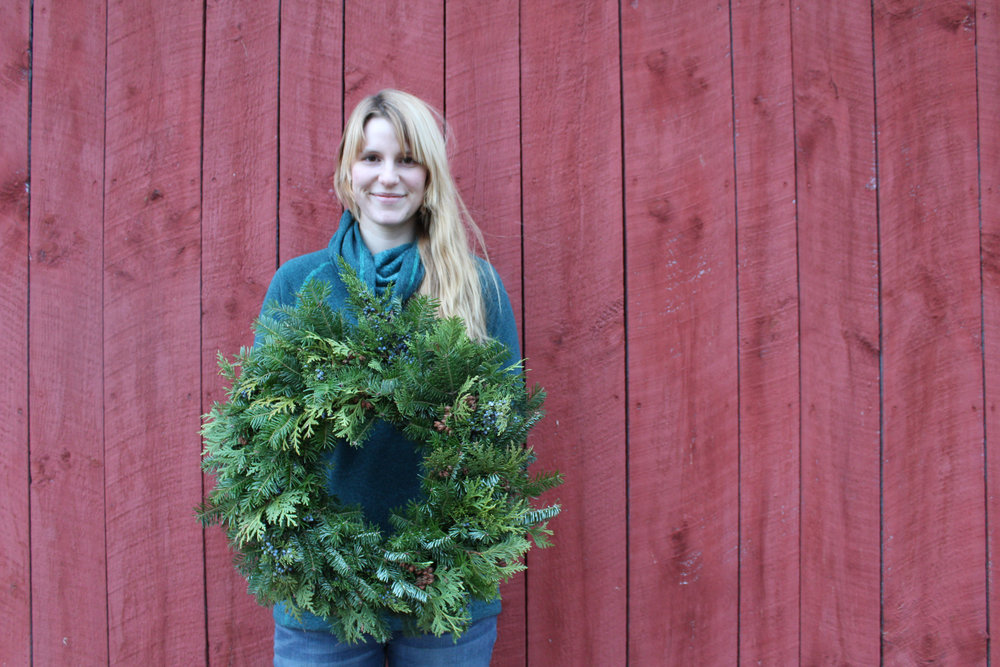 Allie, our new employee, holding a beautiful undecorated wreath of balsam, juniper, & cedar.