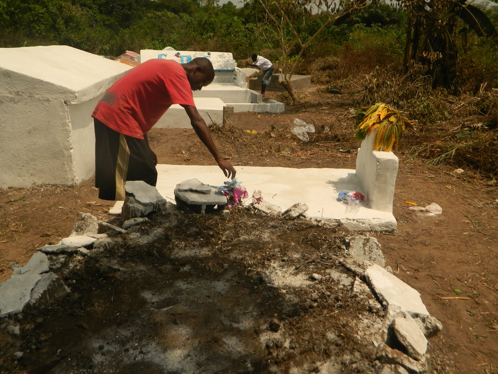 Bettar Howard tends to the grave of his mother in Unification Cemetery in Monrovia on 11 March. (Prince Collins/IRIN)