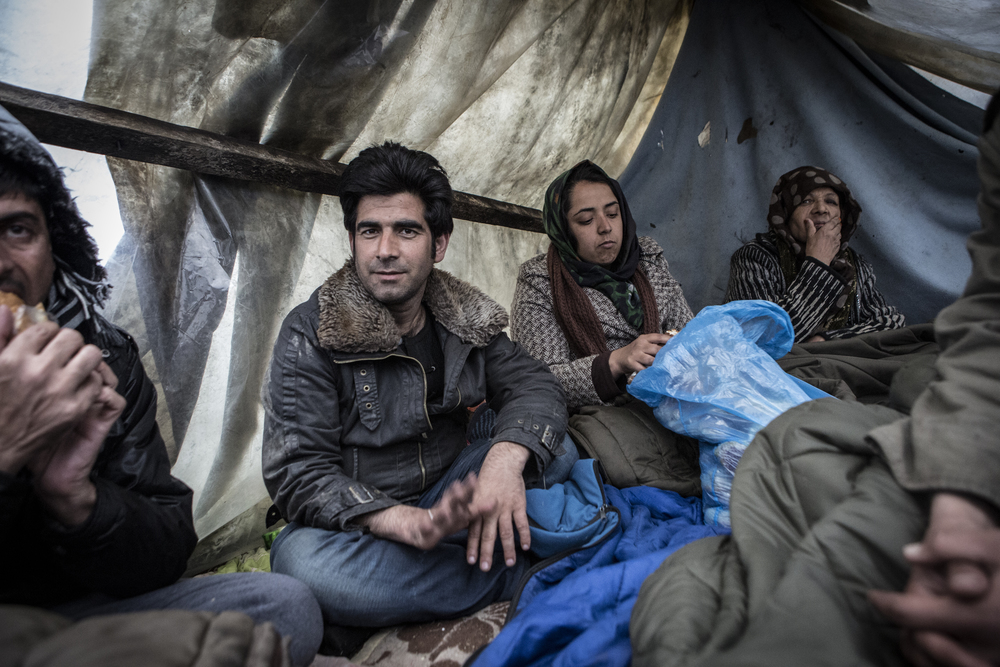 Afghan refugees sit under a plastic shelter in Subotica eating sandwiches donated by a local man.