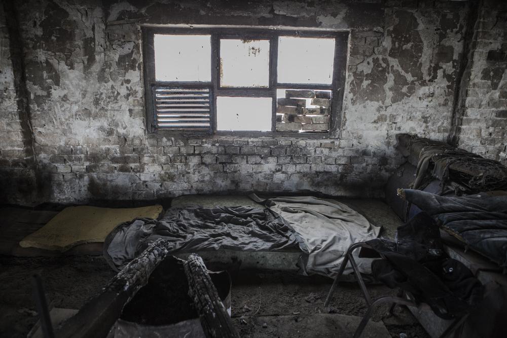 يمكن ملاحظة البطانيات ونار التدفئة التي تم تركها في المكان الذي كان المهاجرون ينامون فيه في الطابق الأول من مصنع الطوب القديم في سوبوتيتسا