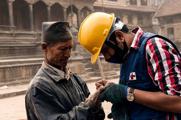 An aid worker from the Red Cross tends to an injured Nepalese man