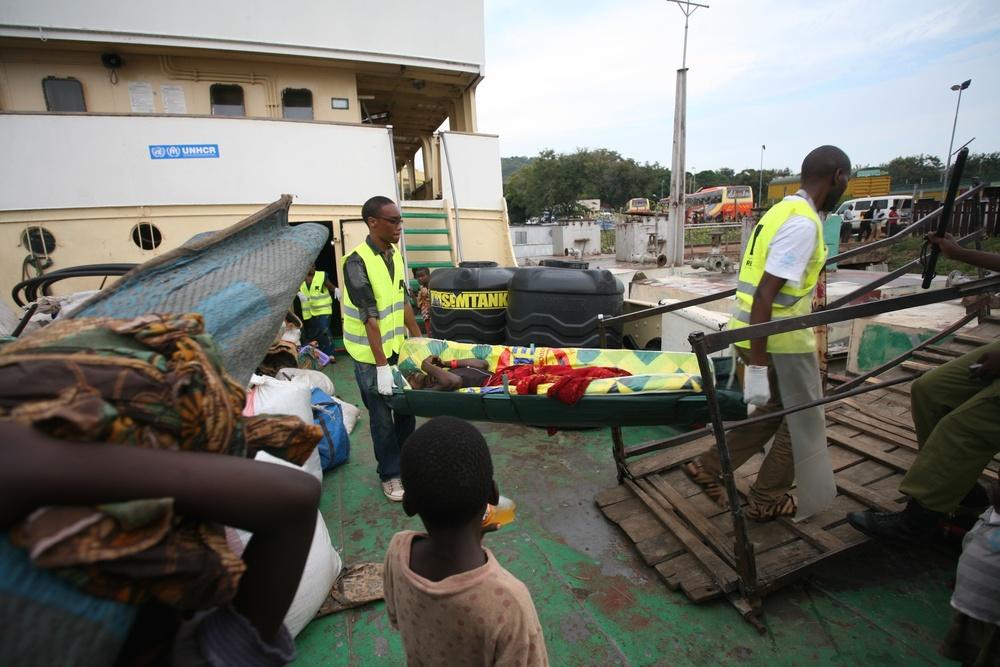 Un réfugié burundais soupçonné d'être atteint de choléra est débarqué du MV Liemba à Kigoma, en Tanzanie, par des employés du Comité international de secours.