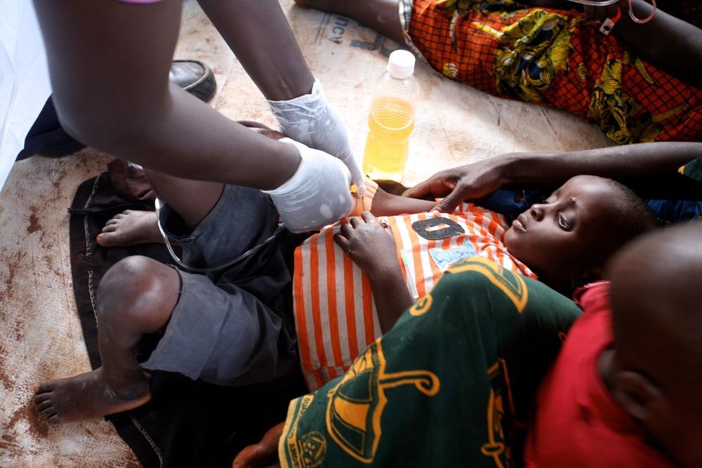 Un réfugié burundais soupçonné d'être atteint de choléra se voit administrée une solution de réhydratation par voie intraveineuse au dispensaire du stade du lac Tanganyika, à Kigoma, en Tanzanie.