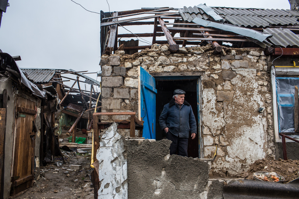 Ivan Kubarev, 61, shows the destroyed home of his elderly relatives in Triokhizbenka, who are now sheltering with him and his wife nearby. (Brendan Hoffman for Mercy Corps)