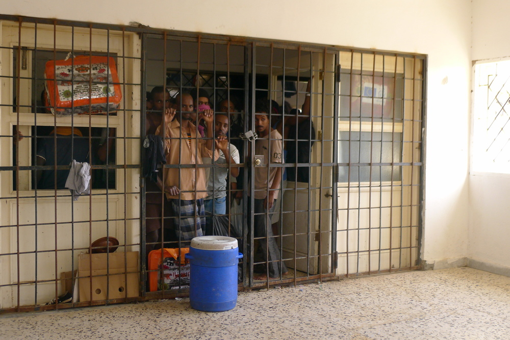 مهاجرون يتجمعون وراء مدخل الطابق الأول من مركز الاحتجاز.
