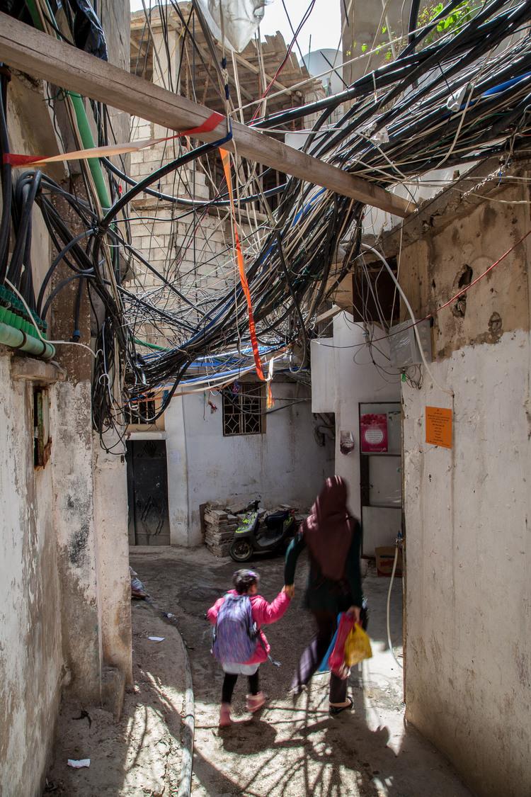 Une femme et une fillette passent sous des câbles et des canalisations dans le camp de Bourj al-Barajneh