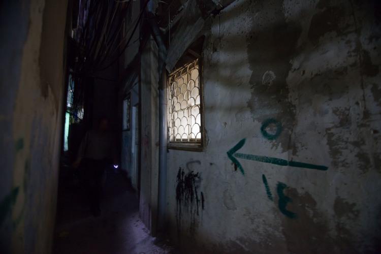 Dans une allée sombre, un homme éclaire son chemin à la lumière d'un porte-clés