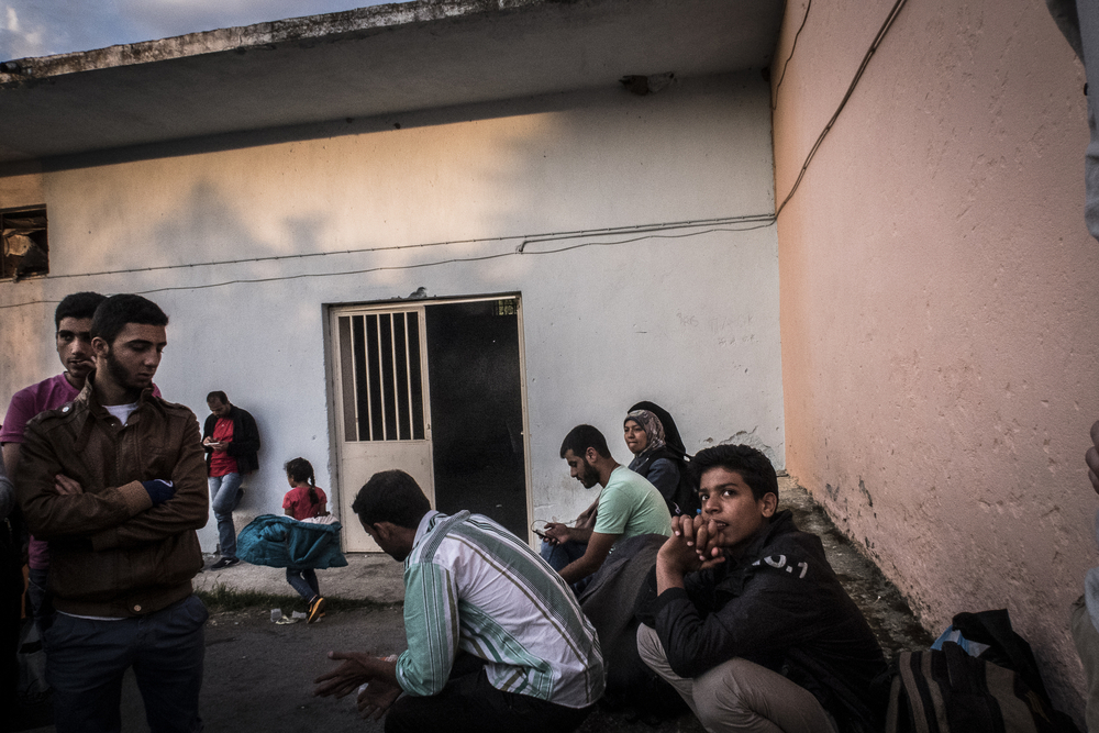 A group of migrants caught by the Greek police get ready for a night at a police station near the border. They will be released the next morning.