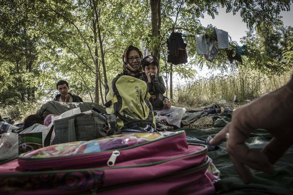 """An Afghan woman and her daughter rest in the border area known as""""the jungle"""" where a criminal gang has been extorting migrants."""
