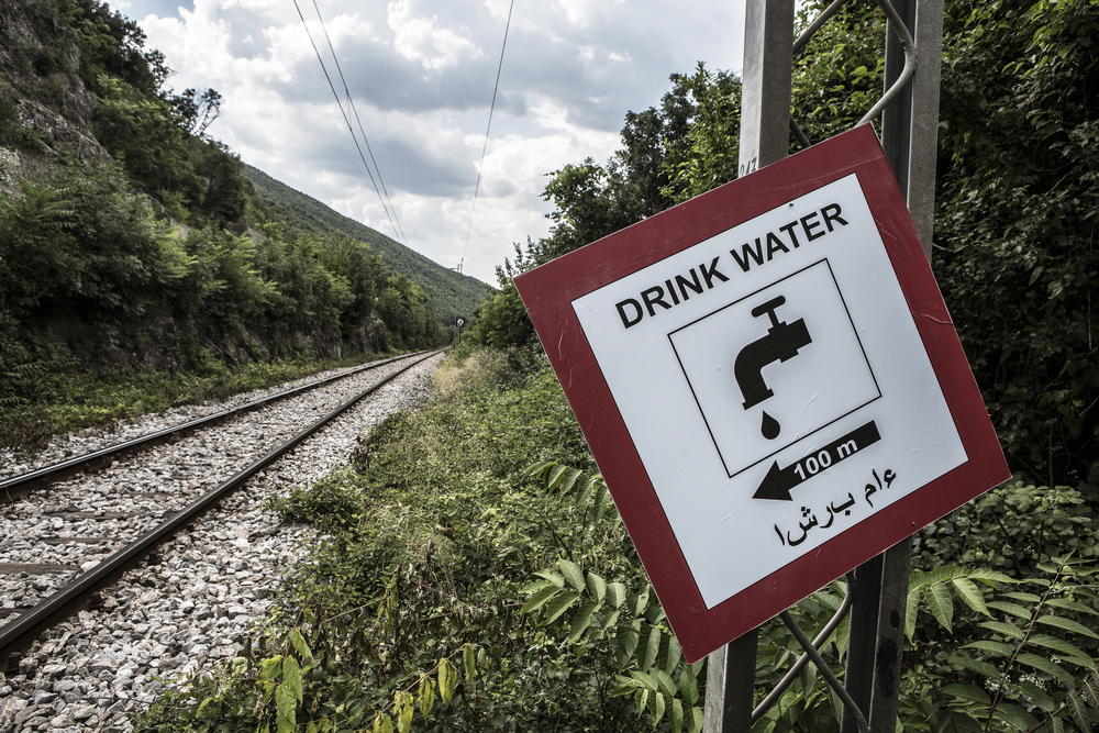 One of the 60 signs that a Macedonian man has put up along the railway line warning migrants of the dangers and directing them to water fountains.
