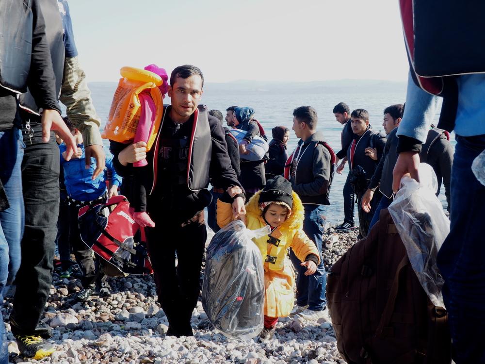 عائلة مهاجرة تهبط إلى الشاطئ في سكلالا سيكامينياس. غالبية الوافدين إلى اليونان من السوريين، يليهم الأفغان (جيولا برتولوتسي/إيرين)