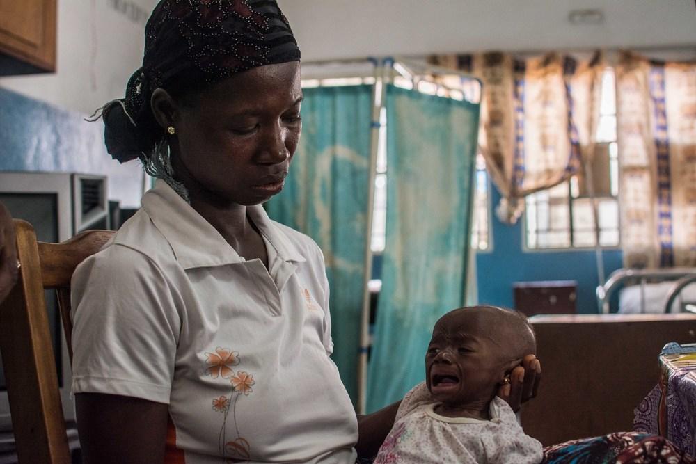 فاتيماتا سانكوه تحمل طفلها المصاب بسوء التغذية الحاد في مستشفى أولا ديورينج للأطفال في شرق فريتاون، حيث ازداد عدد الأطفال الذين يعالجون من سوء التغذية أيضاً منذ تفشي الإيبولا.