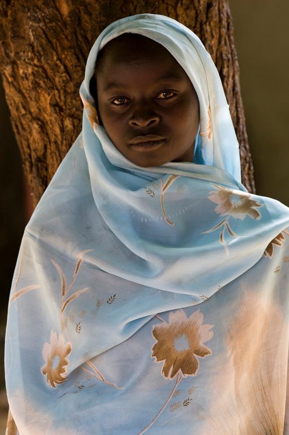 """اضطرت كيني هوى عبد الله، التي تبلغ من العمر   17   عاماً، للعمل كبائعة متجولة في السوق المركزي في بلدة كاودا. وهي تتساءل: """"لماذا يقصف البشير مدارسنا؟ لماذا لا يريد أحد مساعدتنا بتوفير الكتب المدرسية حتى نتمكن من الاستمرار في دراستنا؟""""    (جيوفاني ديفيدنتي)"""