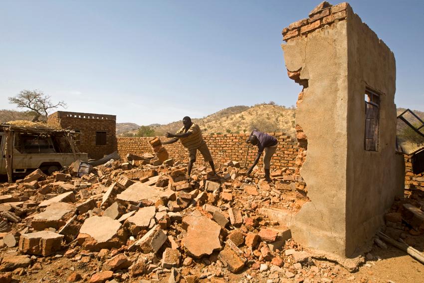مدنيون يقفون فوق حفرة أحدثتها قنبلة أسقطتها قوات الحكومة السودانية في جنوب كردفان، السودان، 17 يونيو 2013.