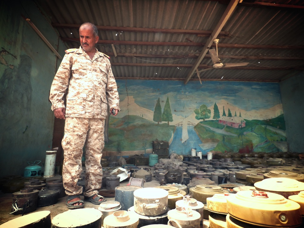 Shiek Zaid Tabet, head of the Mine Action Programme in Aden, stands amid some of the land mines found by his teams since mid-July
