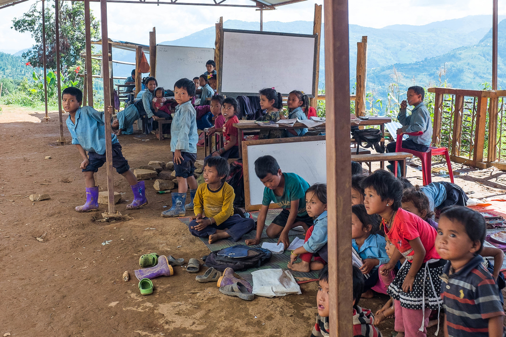 Schoolchildren look at the sky as a relief helicopted flies by on 11 August 2015 in Kiul. The school completely collapsed during the earthquake and students are now attending classes under a metal roof with no walls and only white boards separating each class.