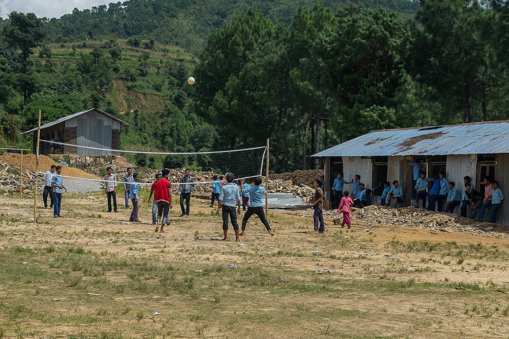 Students play volleyball during a break in classes near the temporary learning center set up on the grounds of their school on 10 August 2015 in Bhotsipa.