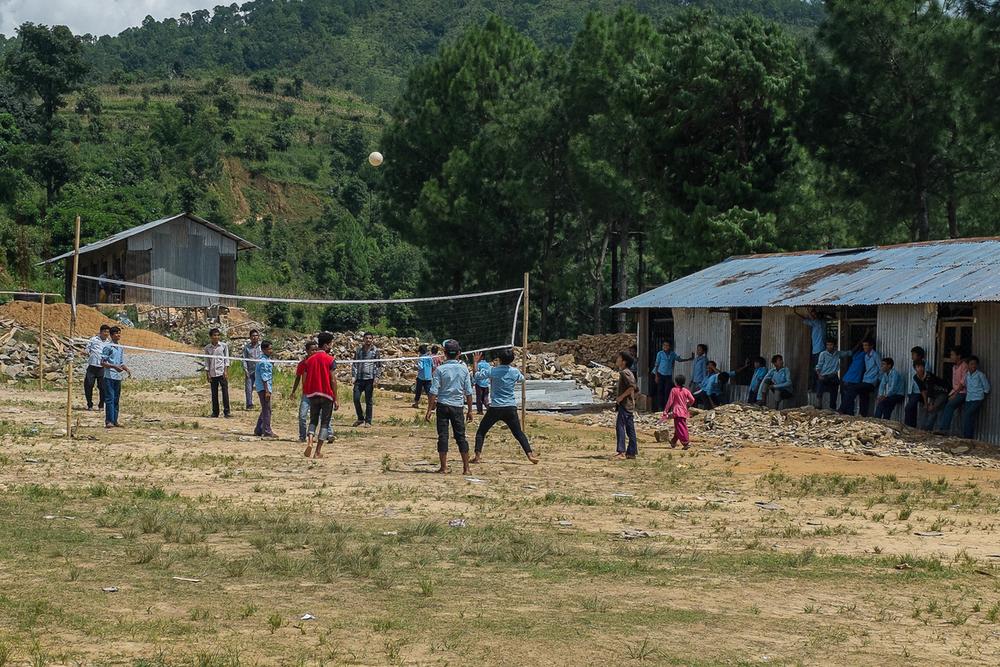 طلاب يلعبون الكرة الطائرة خلال استراحة أثناء الدوام بالقرب من مركز تعلم مؤقت مقام في حرم مدرستهم في 10 أغسطس 2015 في بوتسيبا.