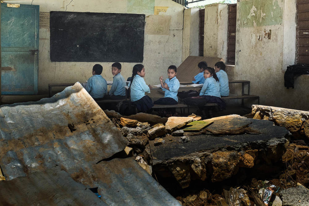طلاب يحضرون الفصول الدراسية يوم 10 أغسطس 2015 في سيبا بوخاري داخل مباني المدرسة التي تضررت جراء الزلزال.