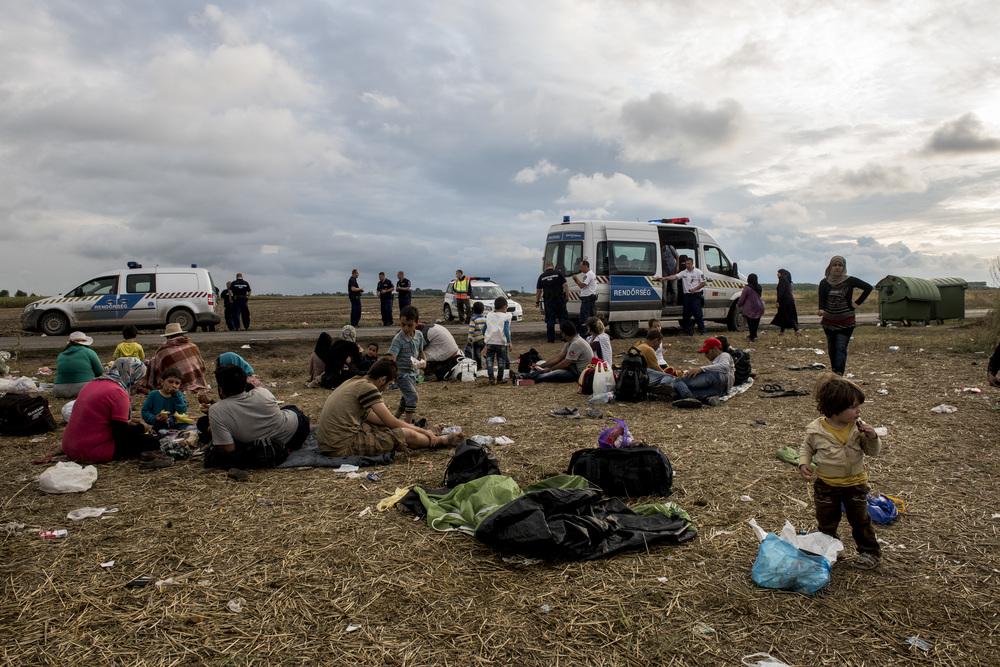اللاجئون الذين تم اعتراضهم ينتظرون وصول حافلة لنقلهم إلى مخيم مؤقت لطالبي اللجوء في بلدة سيغيد القريبة