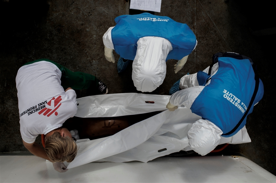 An MSF doctor and Italian officials examine the body of a 15-year-old Somali boy who died on board MSF's Dignity 1 ship after being rescued at sea (Alessio Romenzi/IRIN)