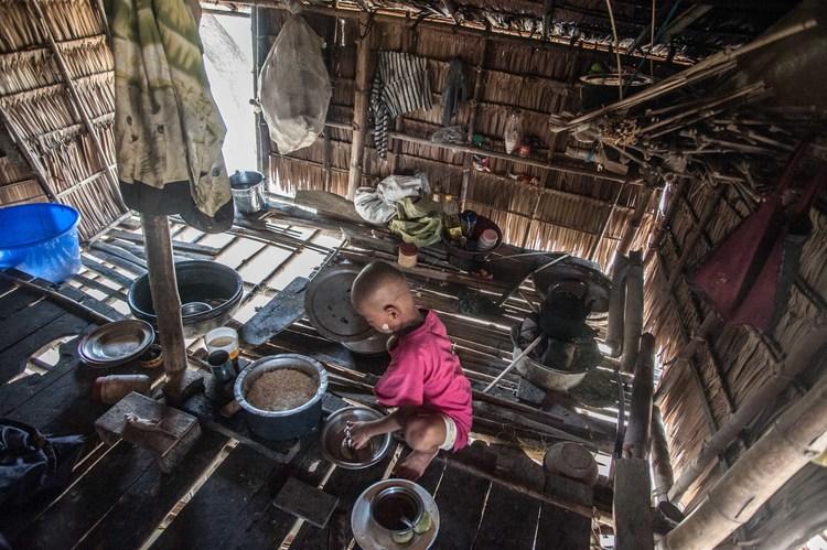 طفل يساعد عائلته في إعداد الطعام في منزله في قرية غاونغ غيي حيث يصبح مزارعو الكفاف في كثير من الأحيان محاصرين في حلقة مفرغة من الديون عندما تفشل محاصيلهم
