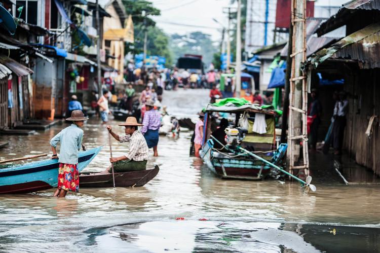أشخاص يشقون طريقهم وسط المياهفي ضواحي باثيين التي تغمرها الفيضانات منذ عدة أشهر