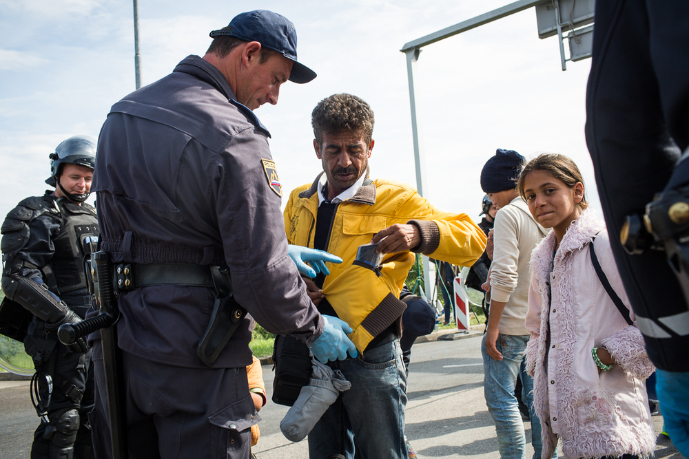Slovenian border police search refugees before they are allowed onto buses at Obrezje.