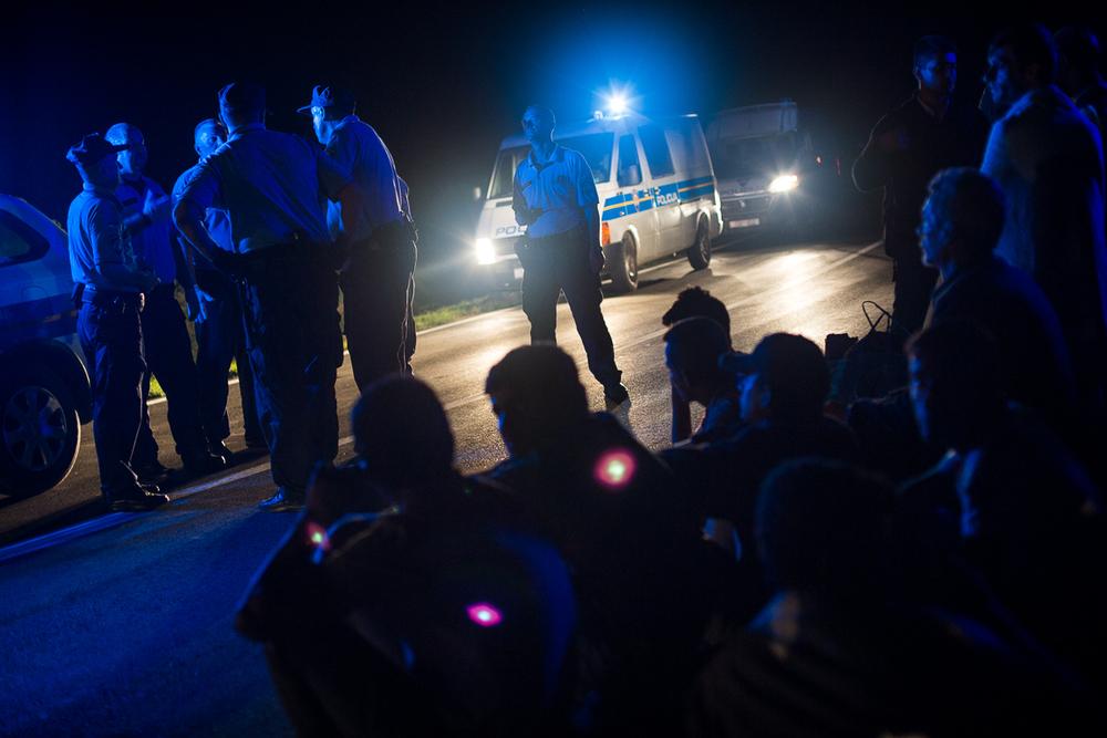 Lassés d'attendre les cars, des réfugiés décident de quitter Tovarnik à pied. Ils sont interceptés par des policiers qui tentent de les convaincre de retourner au village.