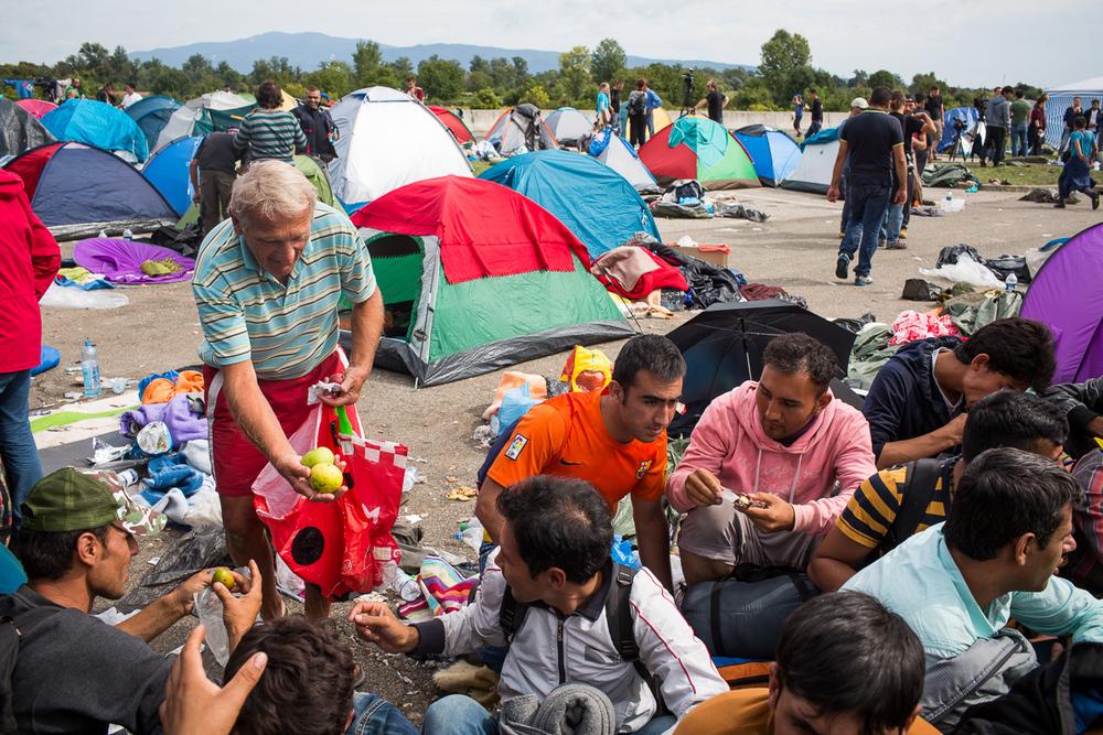 """رجل كرواتي يوزع التفاح على مجموعة من اللاجئين الأفغان الذين أمضوا عدة أيام على الحدود: """"من فضلك، خذ هذه، إنها جيدة جداً!""""."""
