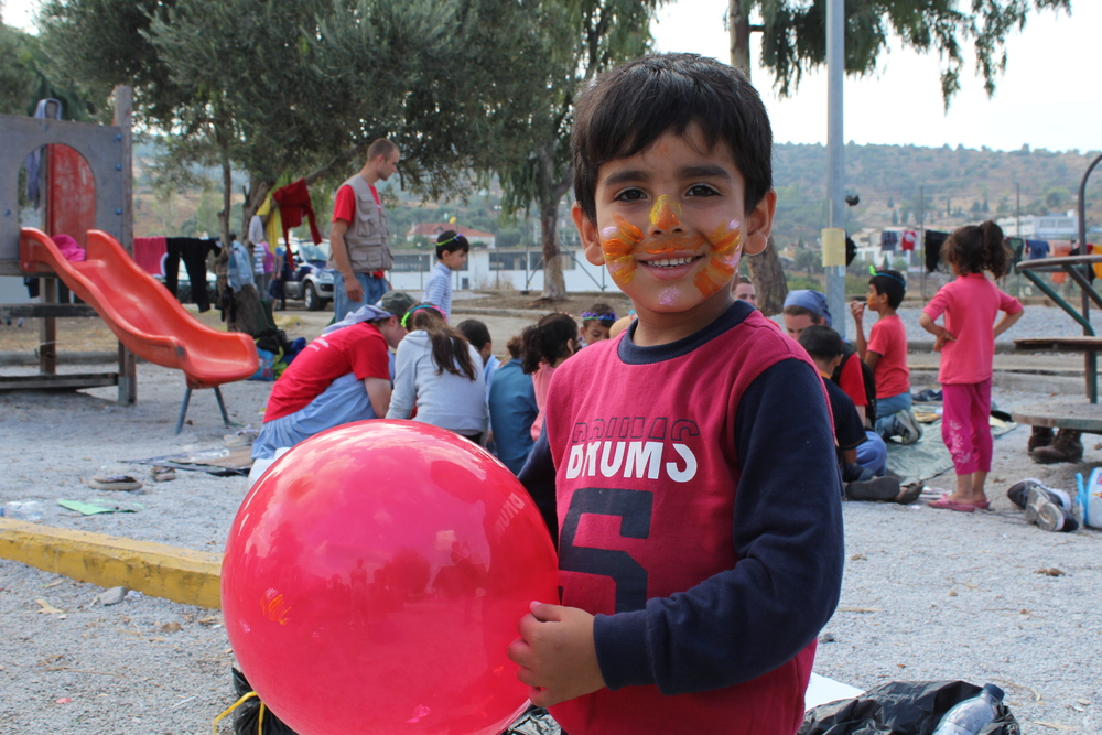 A child plays with a balloon in one of Save the Children's Child Friendly Spaces in Kara Tepe camp, where facepainting is also available for children while their parents wait in line. There are no Child Friendly Spaces in Moria (Daniel Elkan/IRIN)