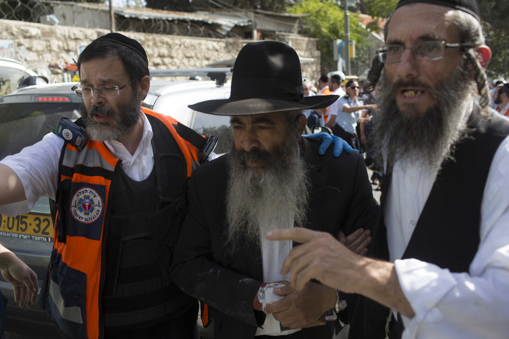 "An Israeli responder from Hatzalah (""rescue"") after a Jerusalem car-ramming attack. Most Hatzalah volunteers are from ultra-Orthodox Jewish communities. Although they are an independent organisation, their certified first responders are trained by MDA and they coordinate response efforts"