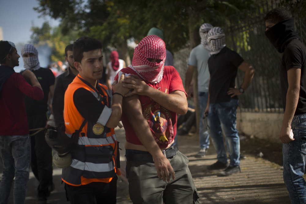 A first responder from the Palestinian Medical Relief Society - a separate organization from the PRCS - tends to the wounded during a Bethlehem skirmish. Clashes with the Israeli army in the West Bank have left many injured by rubber bullets and tear gas