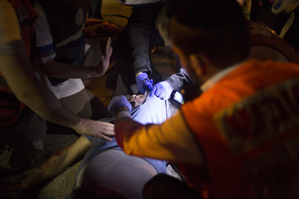 """يقوم متطوعو نجمة داوود الحمراء بعلاج أحد ضحايا عمليات الطعن. """"ماجن ديفيد"""" تعني نجمة داوود، و """"أدوم"""" تعني الحمراء. وقد بثت نجمة داوود الحمراء شريط فيديو يقدم المشورة للمواطنين حول كيفية مساعدة ضحايا عمليات الطعن"""