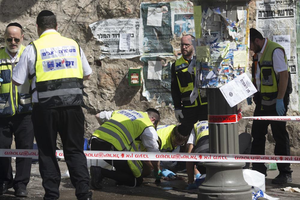 """أعضاء من منظمة زاكا (المتخصصة في تحديد هوية ضحايا الكوارث) يقومون بتنظيف الدماء المتناثرة في المكان الذي تعرض لهجوم في القدس. وعلى الرغم من أن العديد من الأعضاء في زاكا هم من المستجيبين الأوائل، إلا أنهم يكرسون جهودهم لضمان التعامل مع الجثث، وأعضاء أجساد الضحايا، والدم المراق وفقاً للقانون اليهودي. وفي الأسبوع الماضي، أعلنت زاكا أنها ستبدأ في وضع جثث """"الإرهابيين"""" في أكياس سوداء، بدلاً من أكياسها البيضاء المعتادة."""