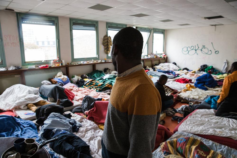 ينامالعشرات من الناس في هذا الفصل الدراسي. ويتم تجميع اللاجئين حسب الجنسية. هؤلاء هم السودانيون