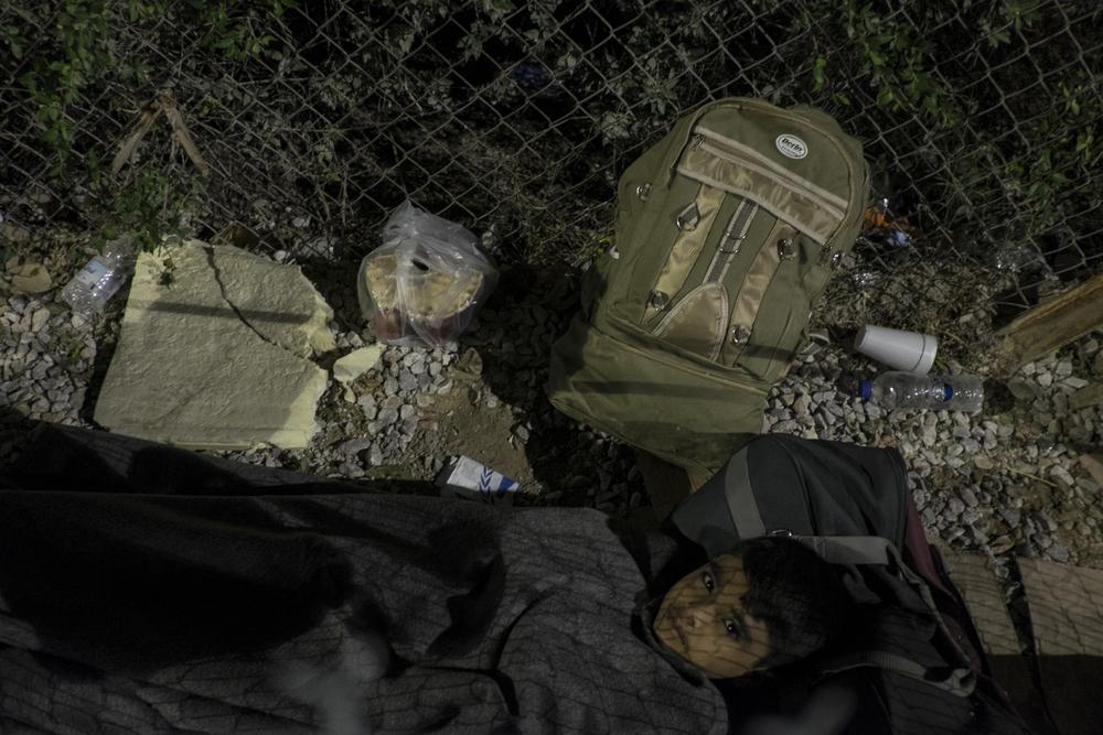 Seul, ce jeune garçon tente de dormir sur un bout de carton à l'extérieur du centre d'accueil de Moria, le long de la clôture