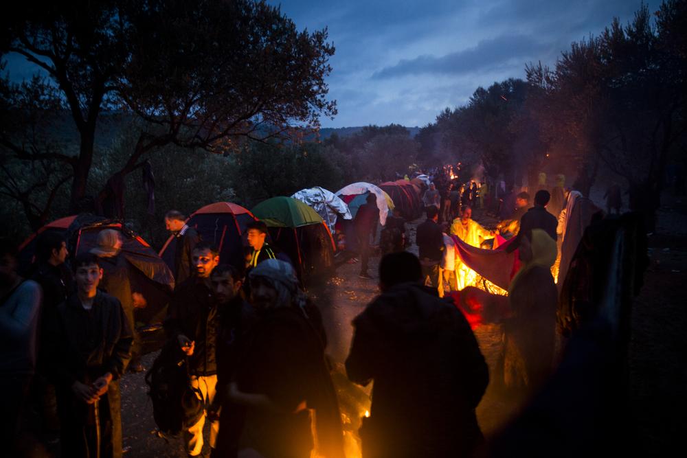 Des réfugiés profitent d'une accalmie pour tenter de se réchauffer et de sécher leurs vêtements