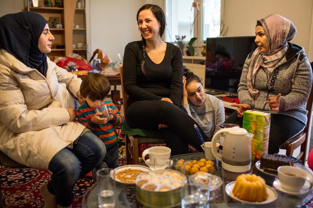نعمت كنعان (في الوسط) وابنتها سارة تستضيفان صديقتان سوريتان في غرفة المعيشة الخاصة بهما (أندريه بونغوفشي/إيرين)