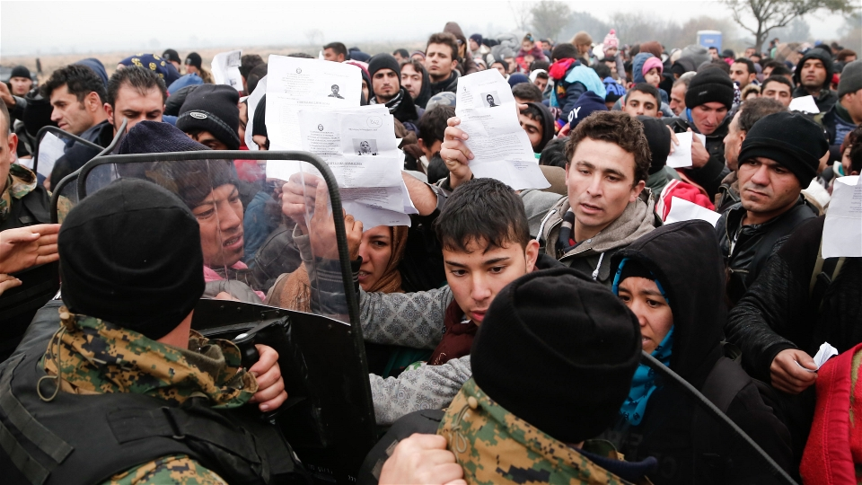 Migrants and refugees wave their Greek registration papers at the border with Macedonia where only certain nationalities were being allowed to cross (Dimitris Tosidis/IRIN)