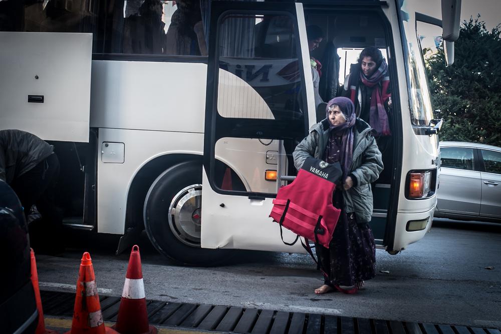 لاجئون ينزلون من حافلة بعد أن تم اعتراضها من قبل قوات حرس السواحل وإعادتها إلى إزمير