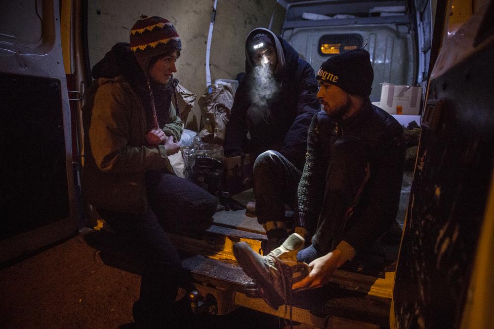 متطوعون ألمان من منظمة أنا إنسان (I'm Human) يمنحون شفيع الله مظفر حذاءً جافاً وجوارب وقفازات وقبعة