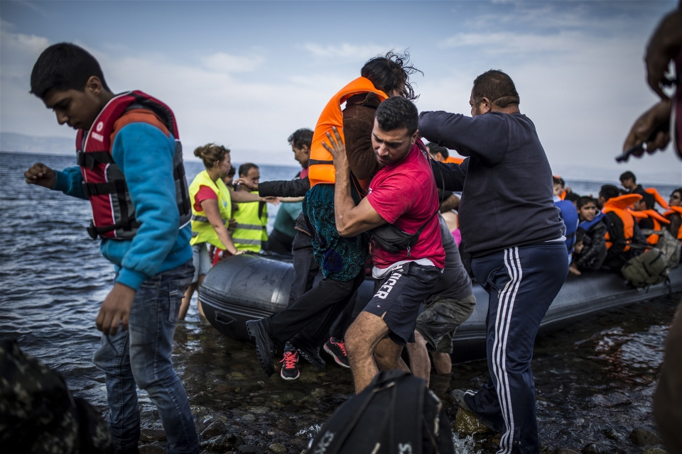 Salam Aldeen of volunteer group Team Humanity helps refugees disembark from a boat arriving on Lesvos (Jodi Hilton/IRIN)