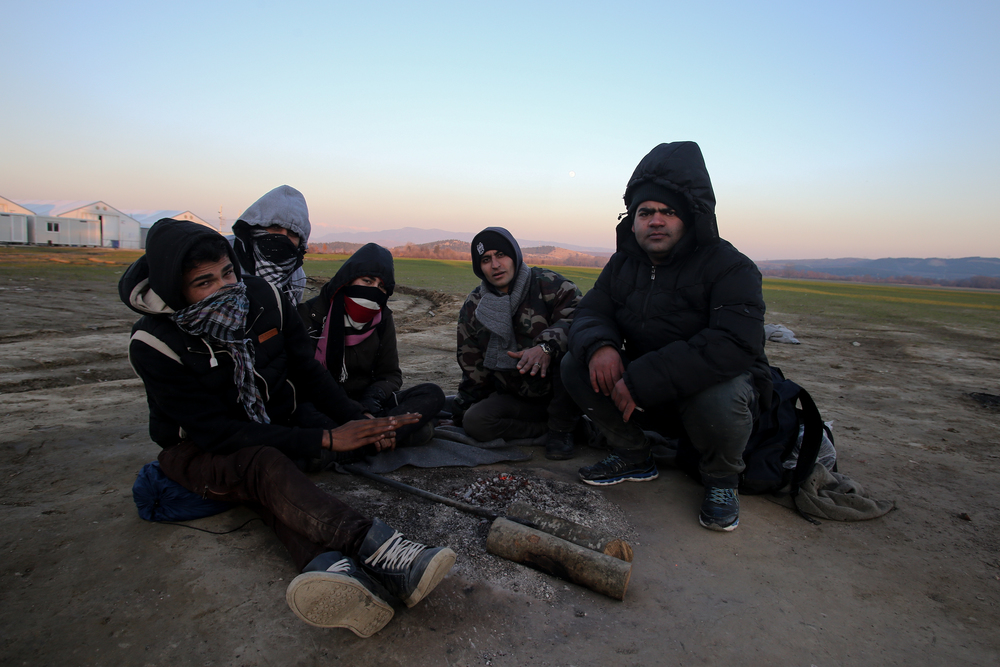 A group of young Iranian migrants who have been stranded at Greece's border with Macedonia for three days, try to keep warm around a small fire. While only Syrians, Afghans and Iraqis are allowed to cross, other nationalities often find alternative, irregular ways.