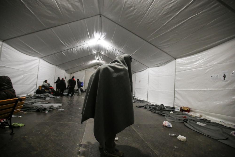 لاجئ يلتحف ببطانية فوق حقيبة الظهر الخاصة به ويلتمس الدفء داخل خيمة مُدفأة في مخيم العبور في ايدوميني