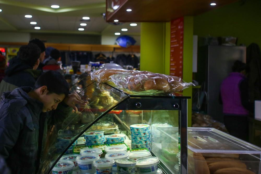 صبي سوري في المقهى الصغير الذي تديره محطة البنزين، التي ترغم الشرطة اليونانية الحافلات التي تقل اللاجئين والمهاجرين على التوقف عندها لأيام في كل مرة قبل استكمال الرحلة إلى الحدود المقدونية. ينتظر العديدون منهم هناك لفترات طويلة يضطرون خلالها لشراء الطعام، على الرغم من وجود غذاء وملابس ومساعدات طبية مجانية في مخيم مؤقت على بعد 20 كيلومتراً