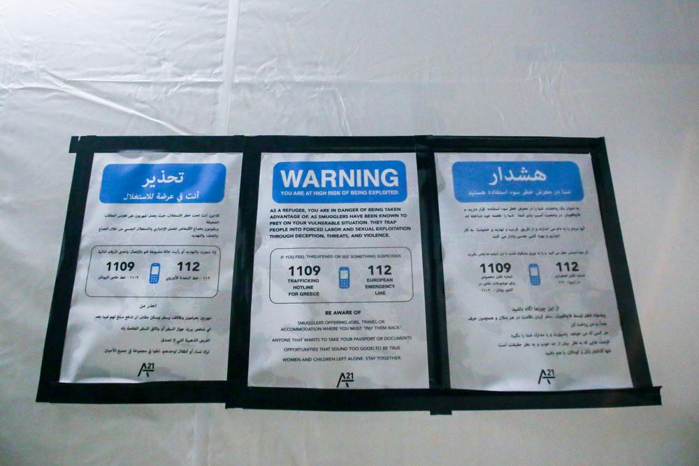 لافتة خارج خيمة في مخيم العبور في ايدوميني تحذر اللاجئين من مخاطر الاستعانة بمهربين وتوفر رقم الخط الساخن للإبلاغ عن أنشطتهم