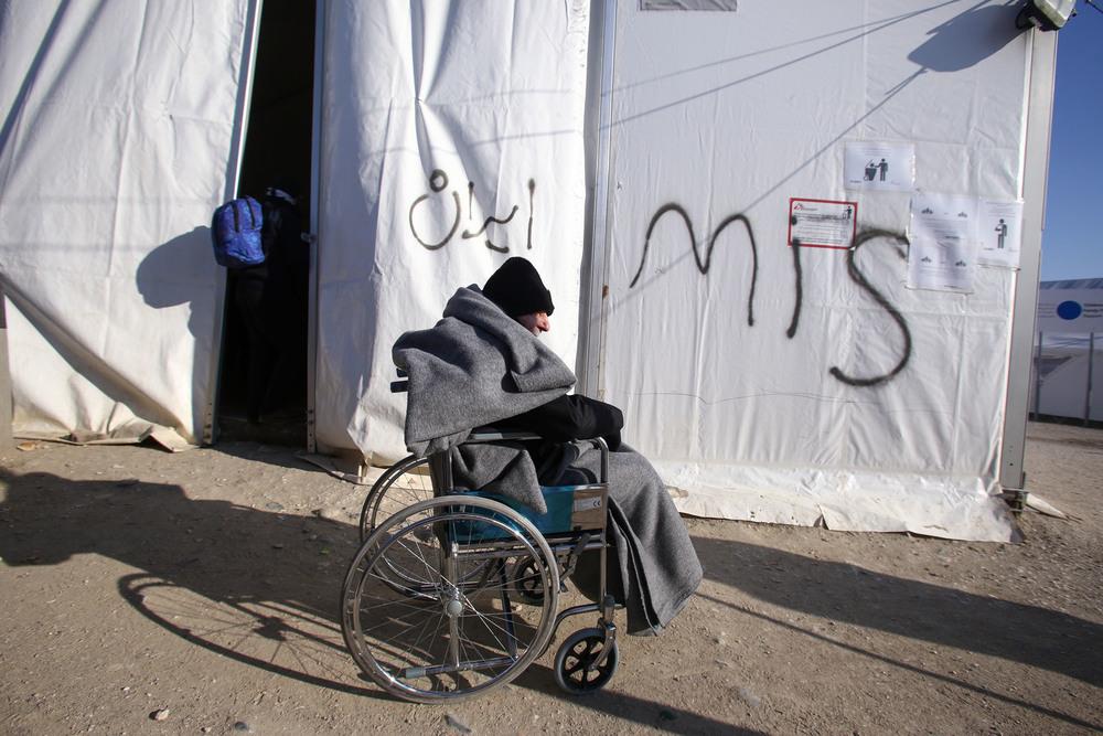 Un réfugié handicapé, emmitouflé contre le froid, devant l'une des tentes que MSF a été autorisé à monter devant une station-service devenue zone d'attente pour les réfugiés et migrants qui tentent d'atteindre la frontière